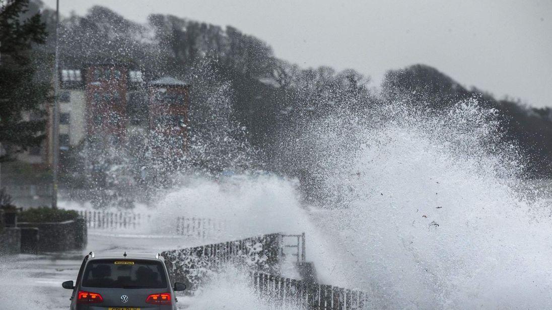 Waves break over a coastal road in Skelmorlie, Scotland