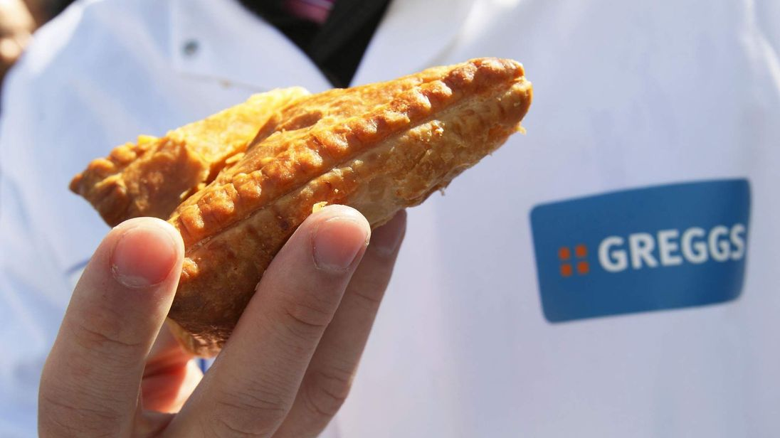 An employee of Greggs bakery holds a pasty