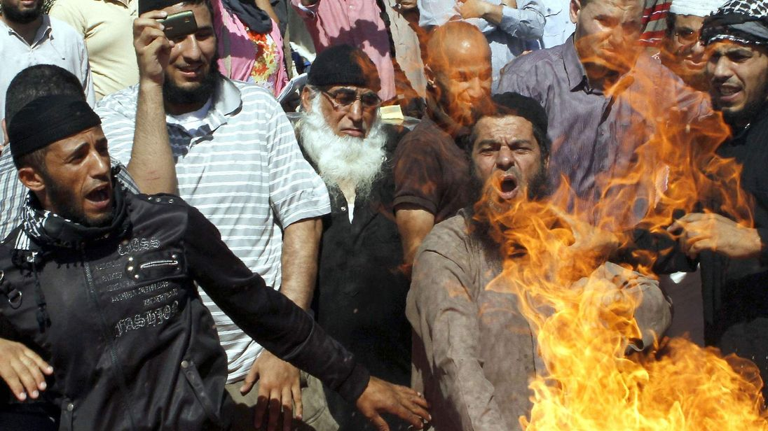Jordanian protesters burn a US flag during a protest against the amateur film Innocence Of Muslims