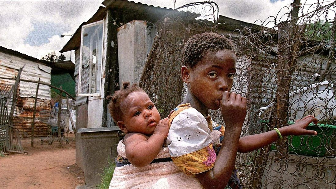 A young girl carries her little sister on her back