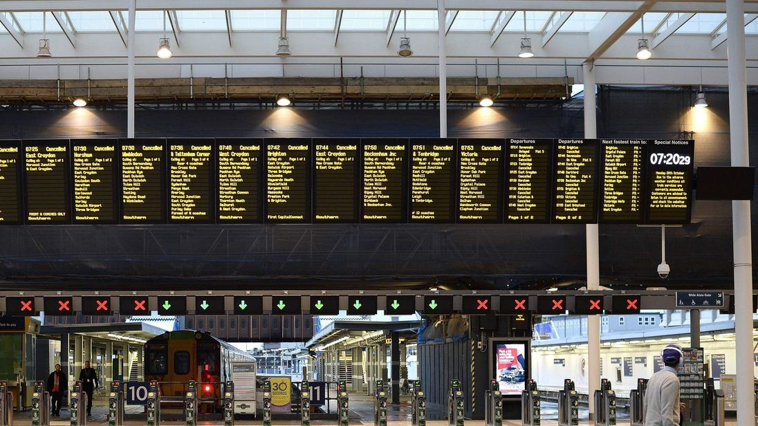 A lone commuter walks past the notice board at London Bridge Station showing all trains cancelled during rush hour in London