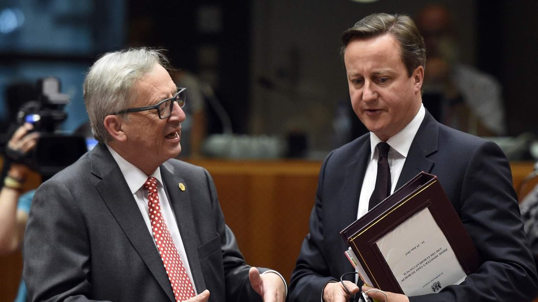European commmission president Jean-Claude Juncker (L) speaks with Prime Minister David Cameron