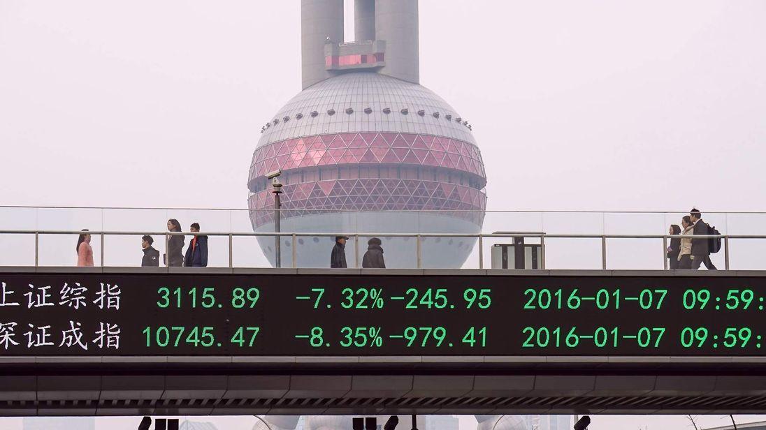 People walk along a bridge with a screen showing stock market movements in Shanghai