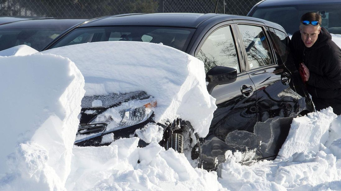 Ben Tippins, at Enterprise/Alamo rental car employee pushes as someone else drives one of over 500 rental cars buried in snow, at Dulles International Airport(IAD) January 25, 2016, outside Washington, DC