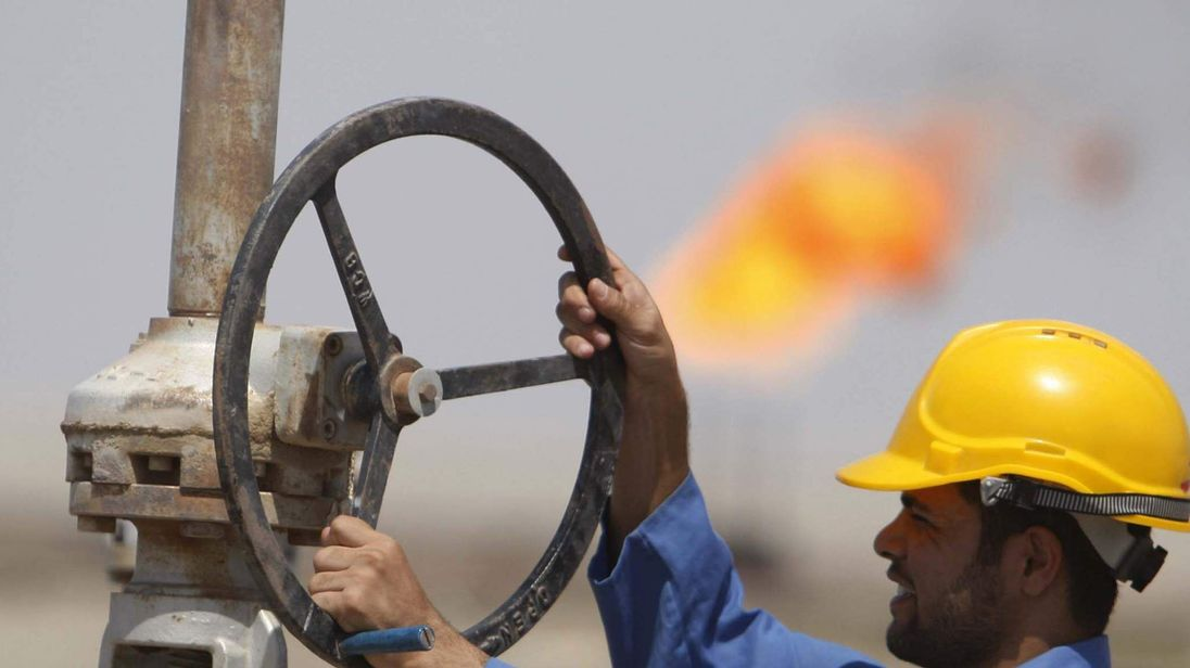 A worker adjusts a pipe at the Nassiriya oilfield in Nassiriya
