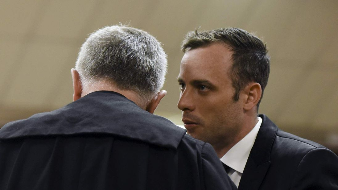 Oscar Pistorius speaks to his lawyer Barry Roux