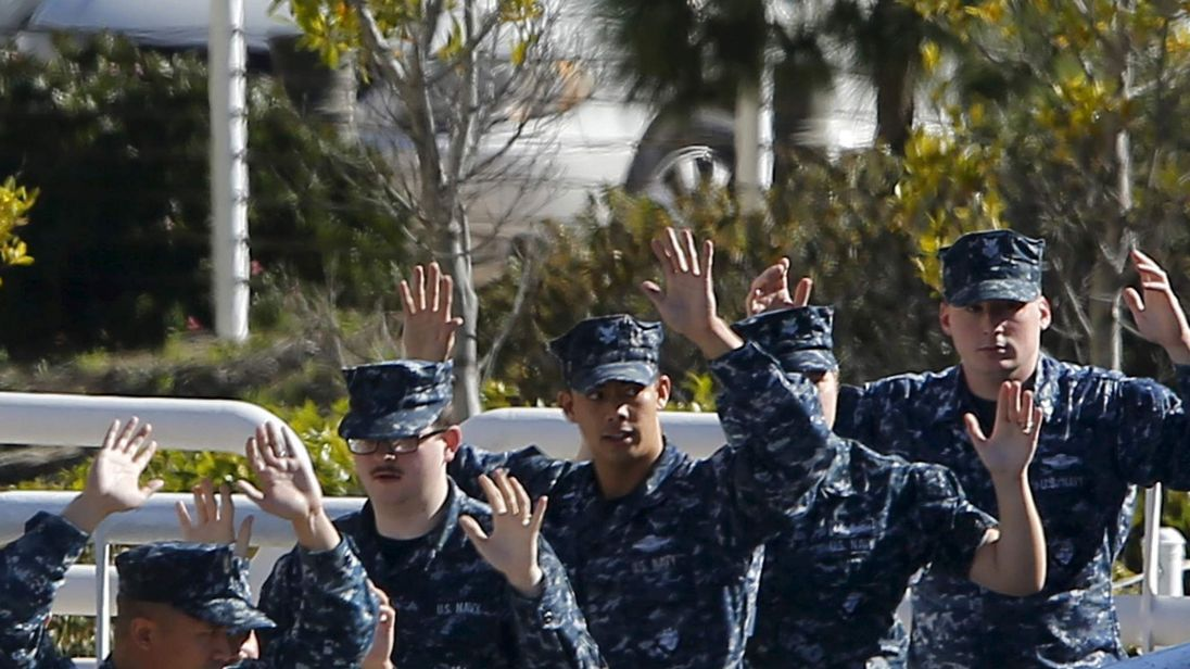 Navy personnel  leave a building with their arms up as a SWAT team clears a building adjacent to Building 26 at the Naval Medical Center in San Diego,