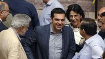 Greek Prime Minister Alexis Tsipras is congratulated by lawmakers after a voting session at the Parliament in Athens