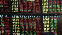 Investors look an electronic board showing stock information at a brokerage house in Shanghai