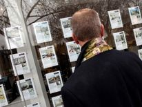 A pedestrian browses properties outside an estate agent.
