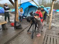 Children in camp play with the Sky News camera