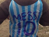 A boy fashions Messi's Argentinian football shirt from a plastic bag