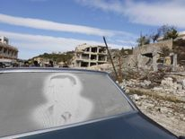 An image of Assad is seen on a car parked in front of damaged buildings in the town of Rabiya