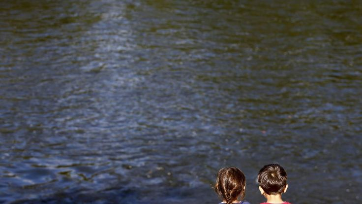 Migrants' children sit at the bank of the river Mur as they wait to cross the border from Slovenia to Bad Radkersburg