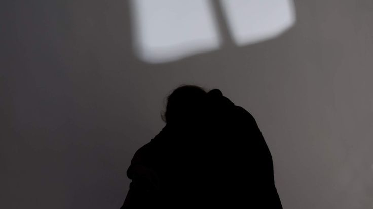 The silhouette of a woman crouching in a corner with a man standing above her