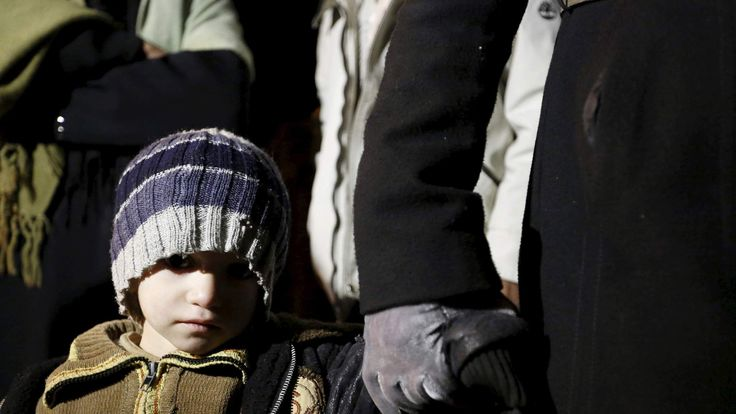 A Syrian boy waits with his family as they depart after an aid convoy entered Madaya
