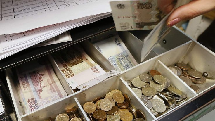 Shop assistant takes Russian rouble banknotes in Krasnoyarsk