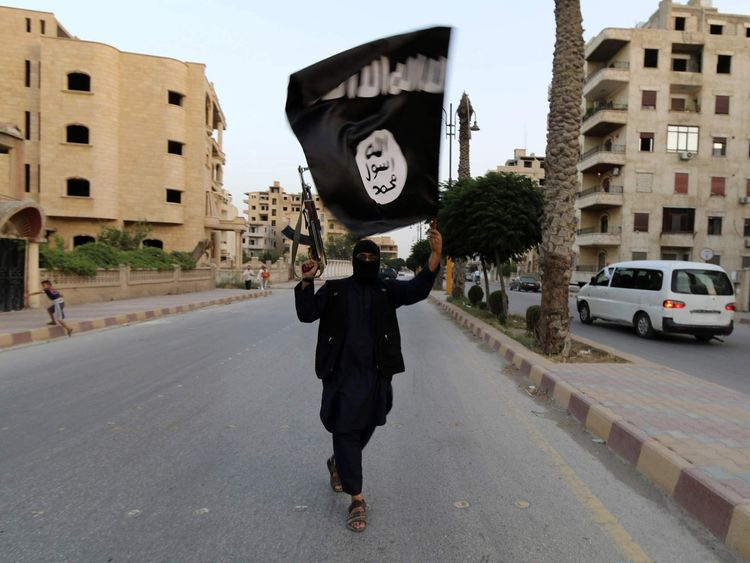 A member loyal to the ISIL waves an ISIL flag in Raqqa, Syria