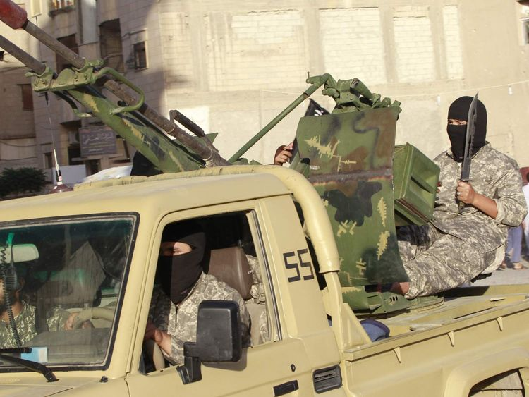 Militant Islamist fighters travel in a vehicle as they take part in a military parade along the streets of Syria's northern Raqqa province