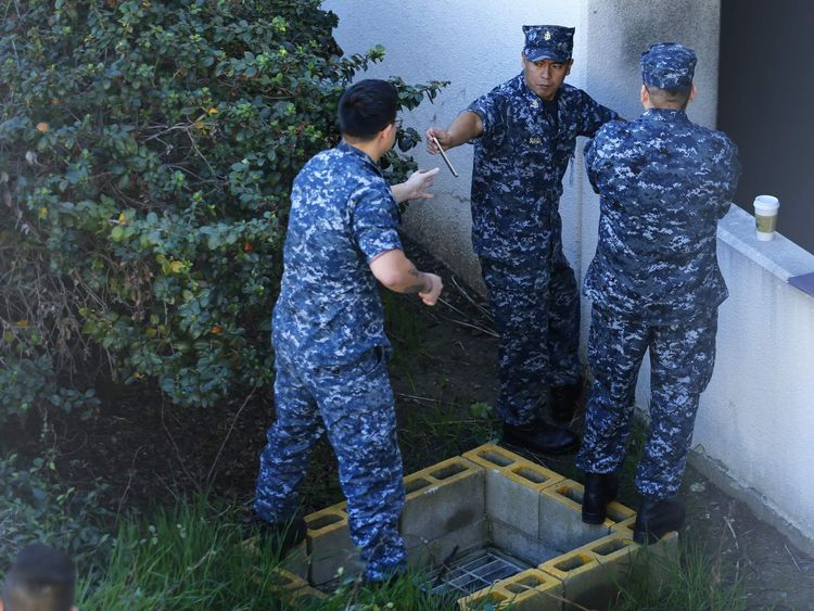Navy personnel converge near parking garage adjacent to Building 26 at the Naval Medical Center in San Diego