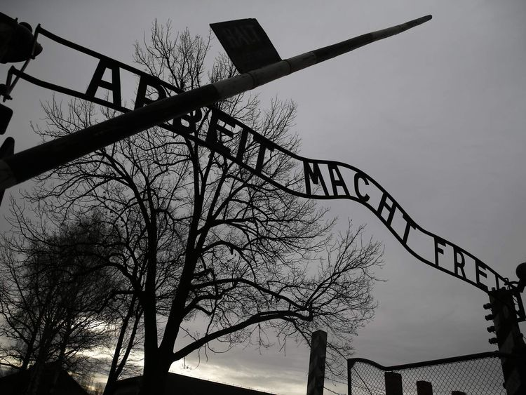 """The Nazi slogan """"Arbeit macht frei"""" (Work sets you free) is pictured at the gates of the former Nazi German concentration and extermination camp Auschwitz-Birkenau in Oswiecim"""