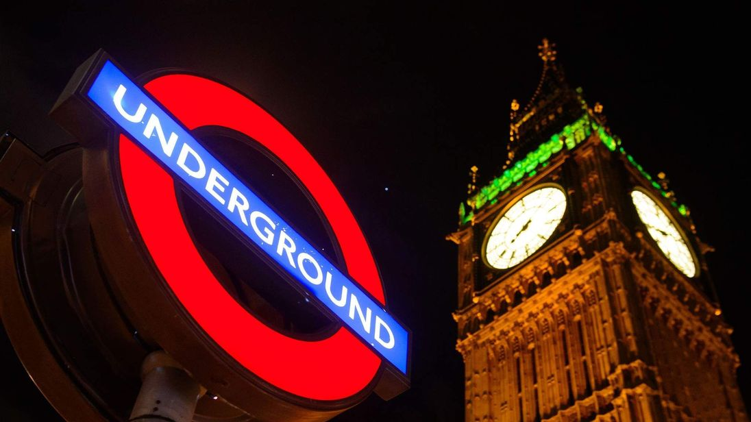 A London Underground sign against the night sky.