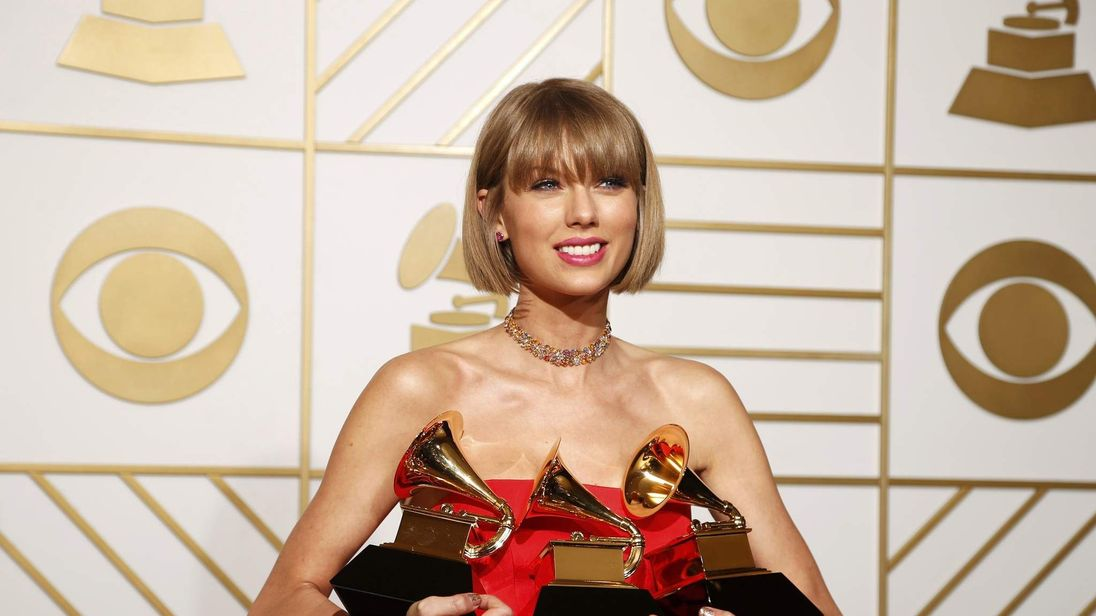 Taylor Swift poses with her awards during the 58th Grammy Awards in Los Angeles