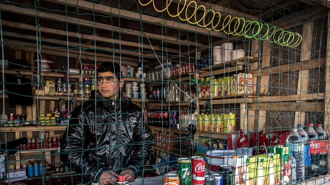 Afghan migrant keeps a makeshift grocery in the migrant camp