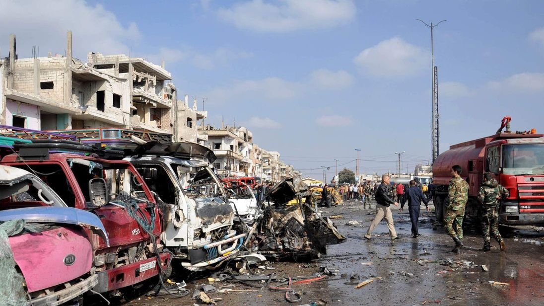 Damaged vehicles at the site of a double car bomb attack in the Al-Zahraa neighborhood of the central Syrian city of Homs