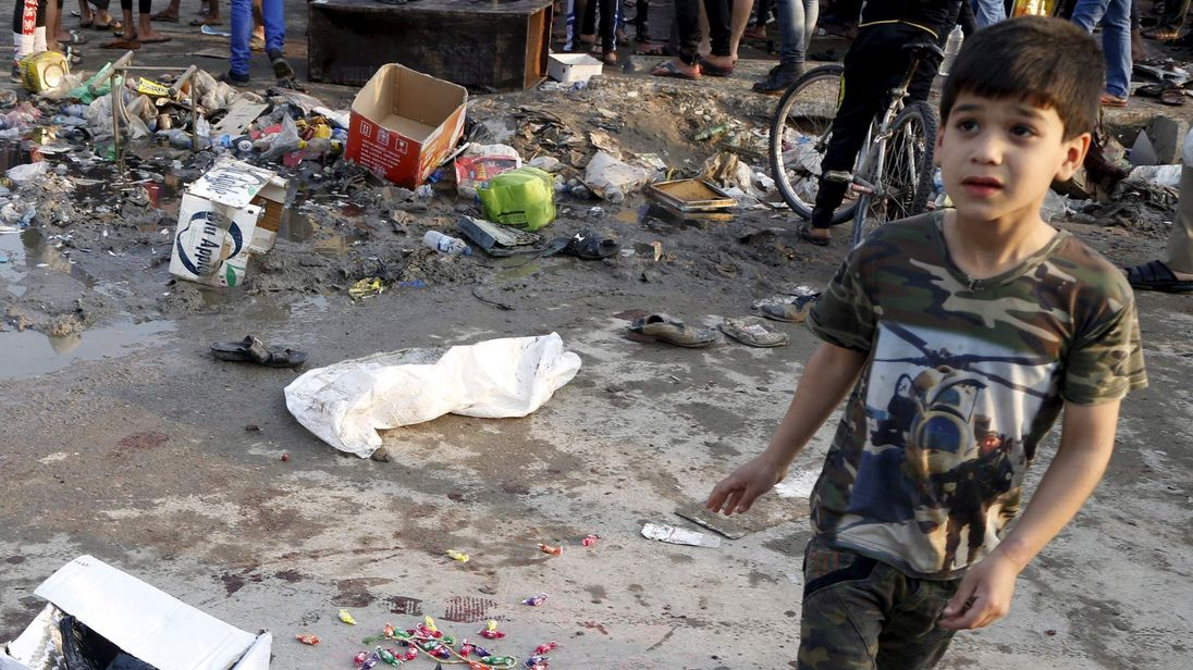 A boy walks at the site of suicide blasts in Baghdad