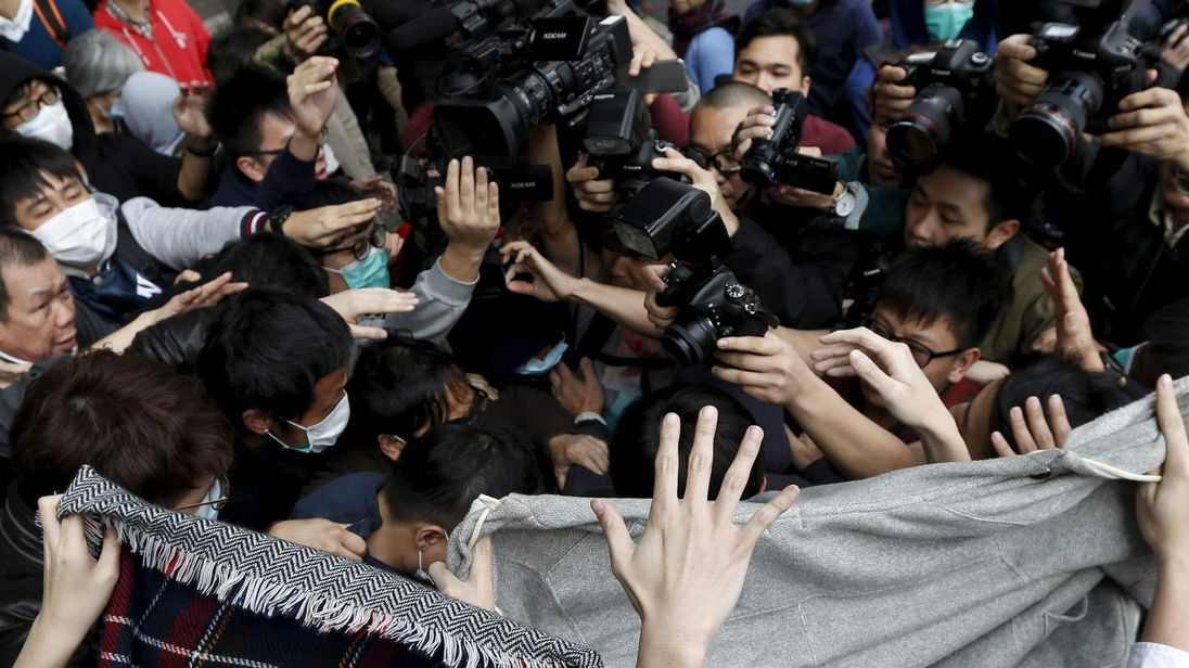 Supporters use cloths to cover a suspect from being filmed by journalists as he leaves to go on bail at a court in Hong Kong