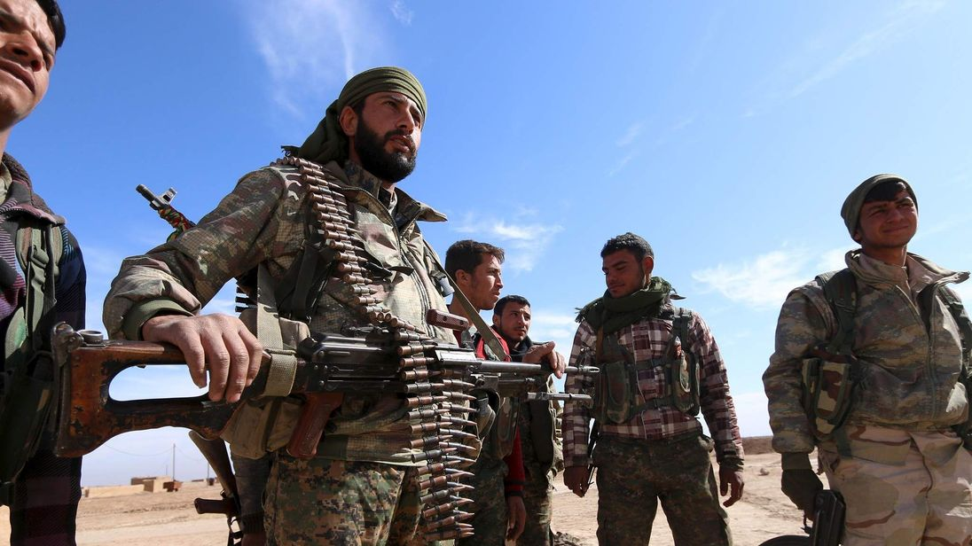 Syria Democratic Forces fighters carry their weapons in a village on the outskirts of al-Shadadi town, Hasaka countryside