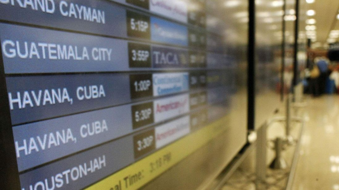 People look at the flight information screens with the last update of flights to Cuba at the Miami International Airport