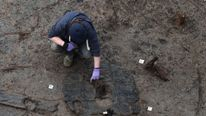 Archaeologists work to extract the earliest complete Bronze Age wheel found in Britain, dated 1100-800 BC