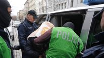 A suspect is detained by plain clothes police during a raid at a house in the Kreuzberg district of Berlin