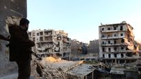 A rebel fighter stands in a building overlooking the damage from fighting in Aleppo