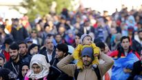 Migrants walk towards the Austrian border after resting in a makeshift camp in the village of Sentilj