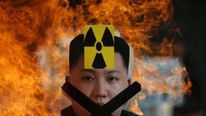 A cut-out of North Korean leader Kim Jong Un is set on fire during an anti-North Korea rally in central Seoul