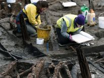 Archaeologists work on the Must Farm site near Peterborough in Cambridgeshire, where the earliest complete Bronze Age wheel has been discovered