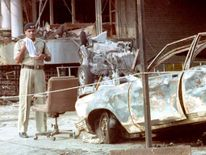 A police officer stands beside a charred automobile