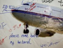 A message left on a board of remembrance by the wife of a passenger aboard missing Malaysia Airlines Flight MH370, at a vigil ahead of the one-year anniversary of its disappearance in Kuala Lumpur