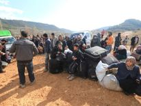 ISyrians fleeing pro-government forces wait to cross the Turkish border