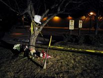 Flowers are placed at a makeshift memorial near a Cracker Barrel restaurant, one of the sites of a series of random shootings that killed six people in Kalamazoo County, Michigan