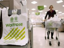 A shopper passes by branded bags in the Canary Wharf store of Waitrose in London.