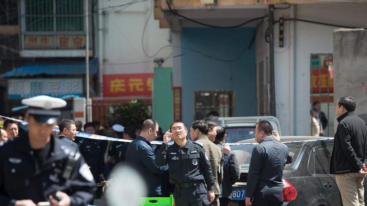 Police cordon off an area outside a primary school where 10 children were stabbed on Monday, in Haikou