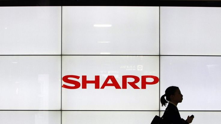 A woman walks past the Sharp Corp's Logo at a train station in Tokyo