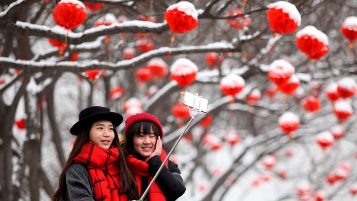 Tourists take selfies after a snowfall in Xi'an