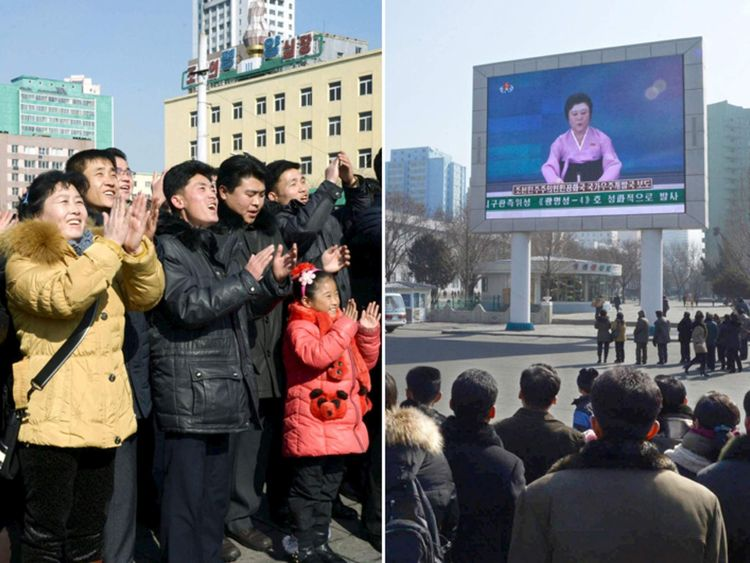 North Koreans watch the launch of a long-range rocket on a giant screen