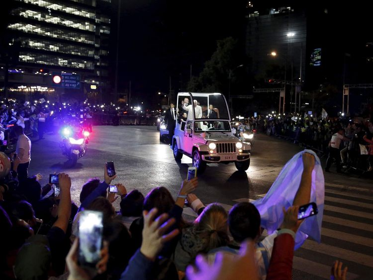 Pope Francis waves to the crowd while riding in the popemobile after his arrival in Mexico City