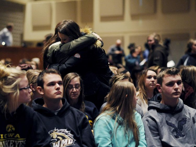 People hug at a vigil after a random shooting killed six people in Kalamazoo County
